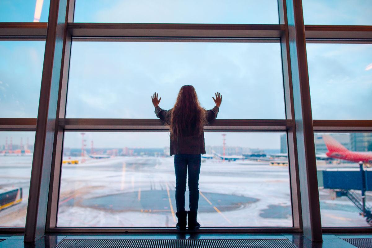 Kleines Mädchen wartet am Flughafen auf das Boarding